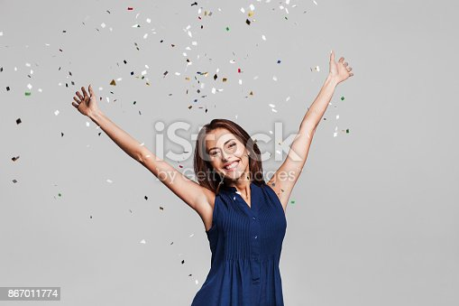 istock Laughing girl with falling confetti at party 867011774