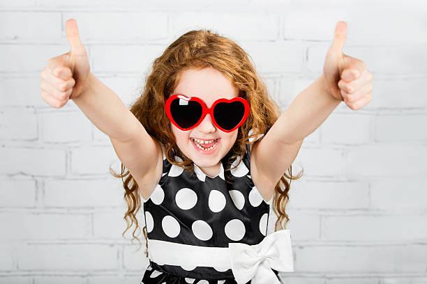 Lachen Mädchen mit Sonnenbrille in Herzform, zeigen Daumen hoch. – Foto