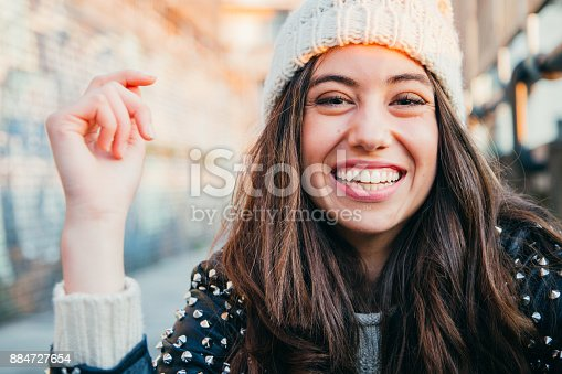 Portrait of a happy and beautiful young woman with woolen cap and lleather jacket laughing