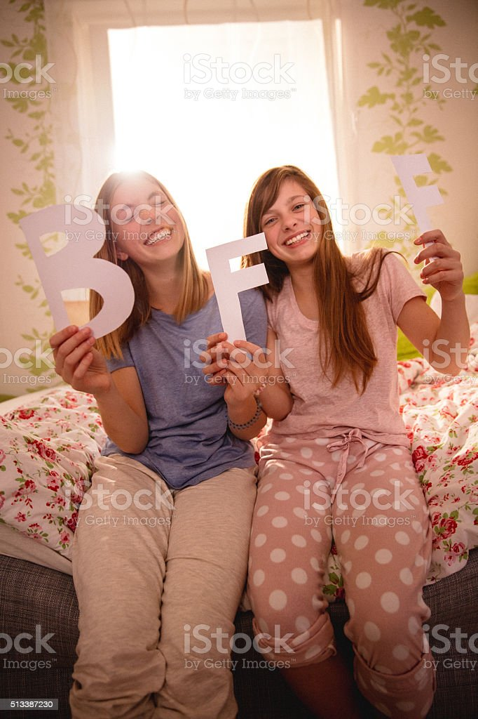 Laughing girls holding the letters BFF for Best Friends Forever stok fotoğrafı