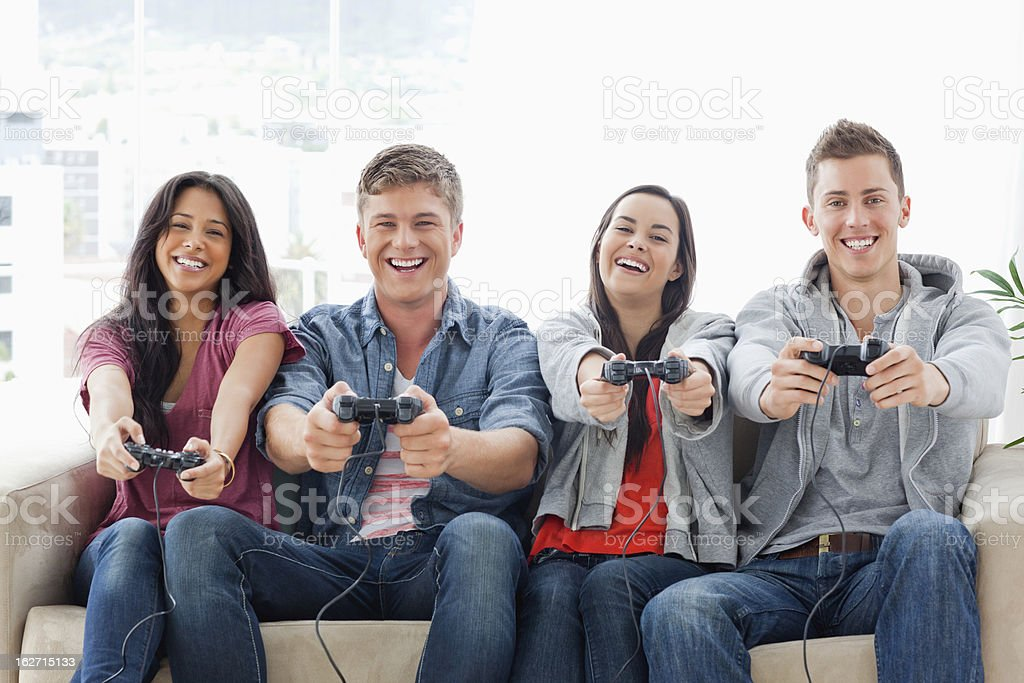 Laughing group enjoying game together while sitting on the c royalty-free stock photo