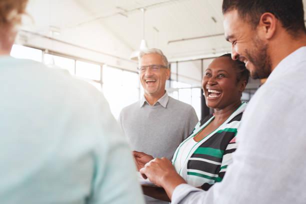 Lachende Gruppe unterschiedlicher Geschäftsleute, die gemeinsam papieren – Foto
