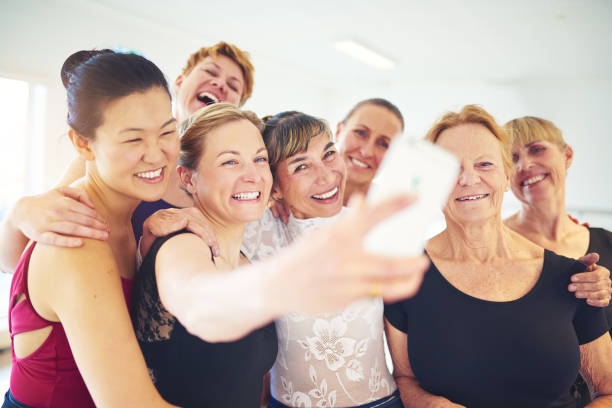 Laughing group of friends taking selfies in a dance class - foto stock