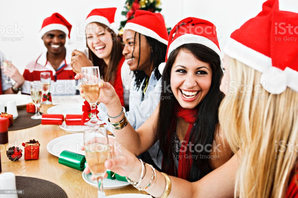 Laughing group of young people round Christmas dinner table royalty-free stock photo