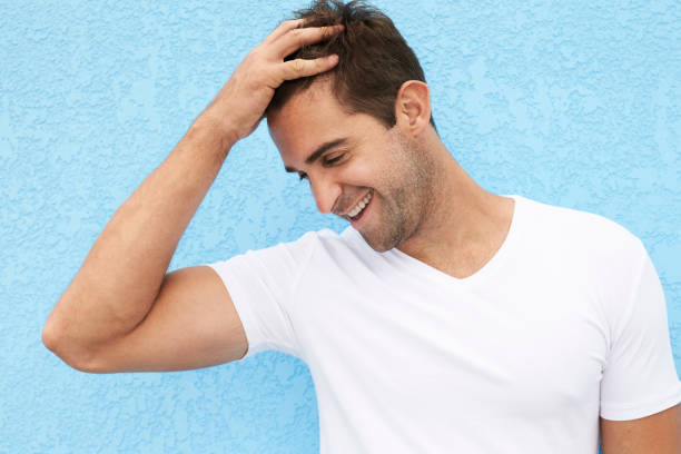 Laughing guy against blue Laughing guy in white against blue background hand in hair stock pictures, royalty-free photos & images