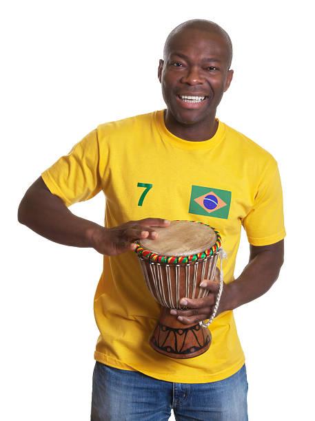 lachen mann aus brasilien mit schlagzeug unterstützt sein team - sambatrommeln stock-fotos und bilder