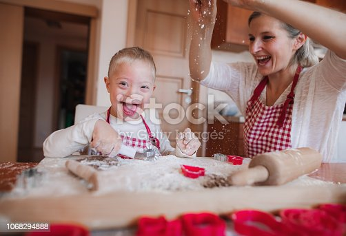 istock A laughing handicapped down syndrome child with his mother indoors baking. 1068294888