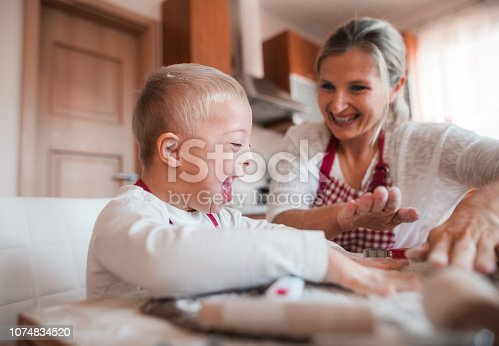 istock A laughing handicapped down syndrome child with his mother indoors baking. 1074834520