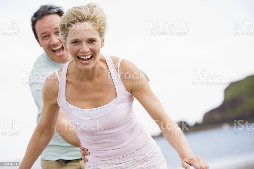 Laughing happy couple playing at the beach royalty-free stock photo