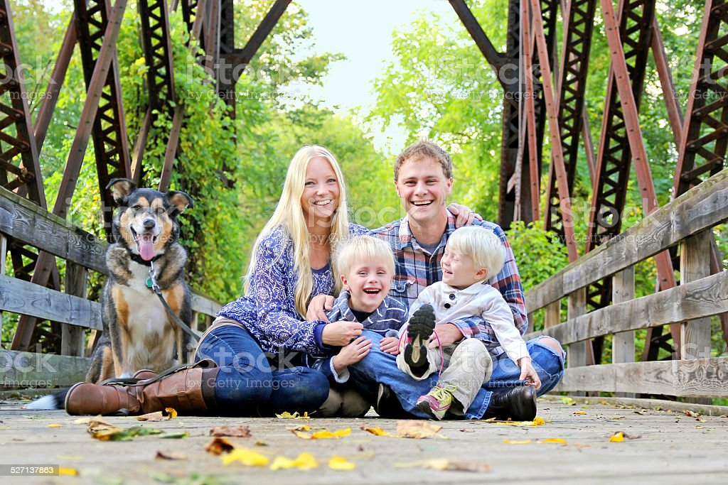 Laughing, Happy Family Sitting on Bridge in Autumn Forest stock photo