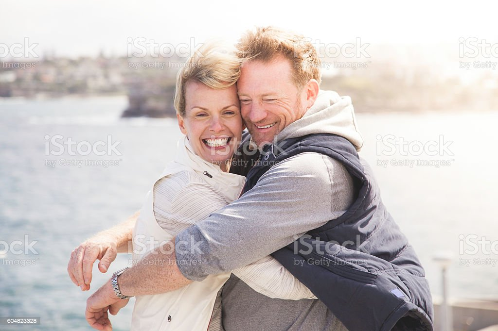 Laughing, happy mature adult couple embracing on windy coastal...