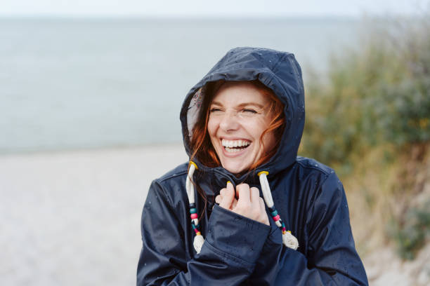 laughing happy woman embracing the cold weather - giacca foto e immagini stock