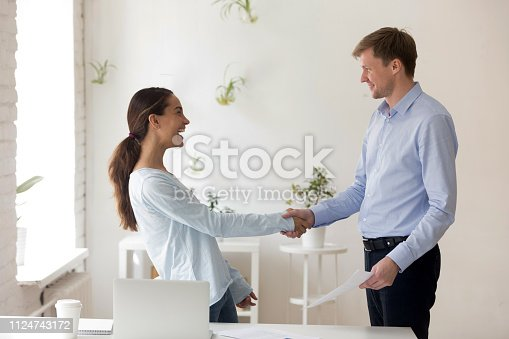 843963182 istock photo Laughing happy woman shaking hand of surprised businessman 1124743172