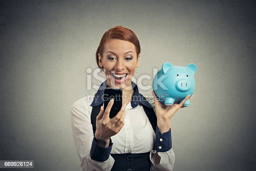 642250754 istock photo Laughing happy young woman holding piggy bank looking at smart phone 669926124