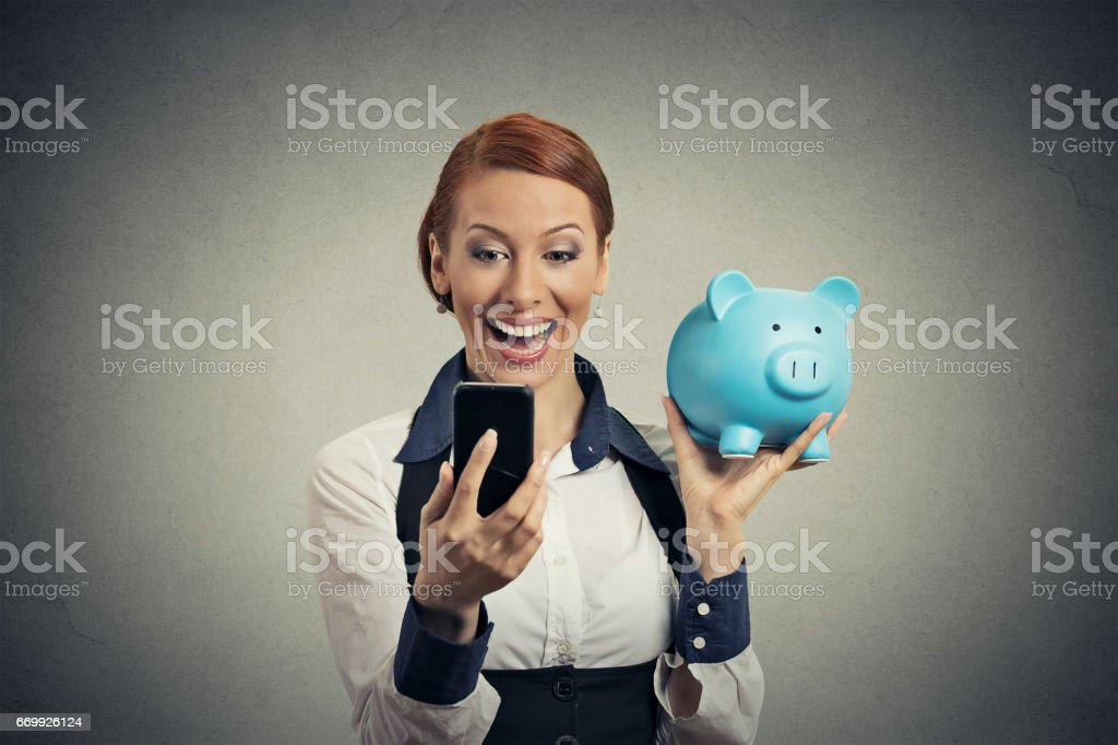 Laughing happy young woman holding piggy bank looking at smart phone stock photo