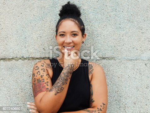istock Laughing hipster girl with tattoos and piercing in urban style 627240650