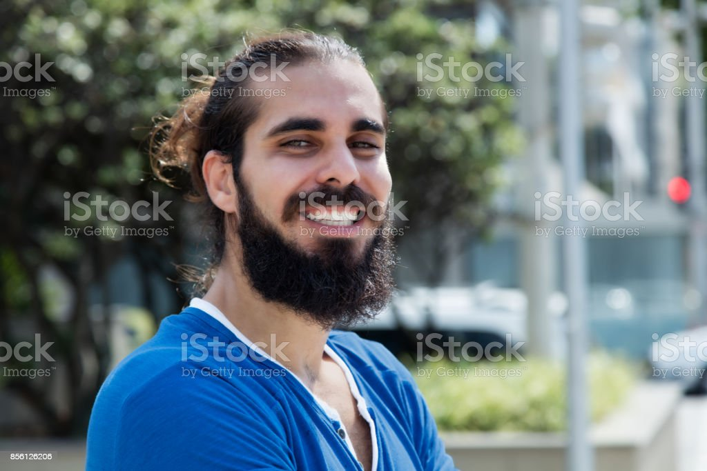 Laughing hipster man with beard and blue shirt in the city stock photo