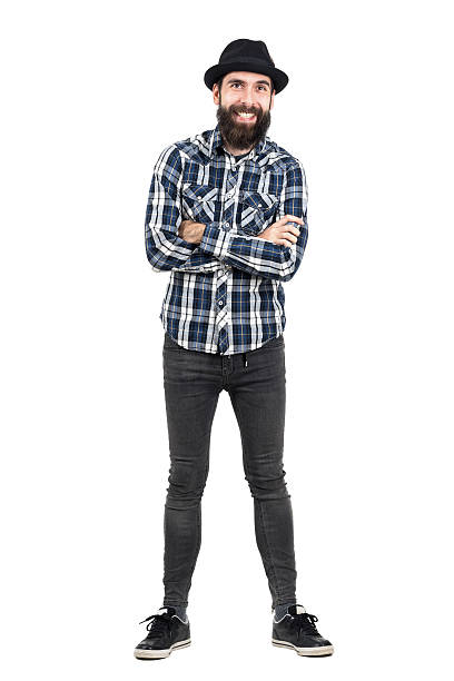 Laughing hipster wearing fedora hat with crossed arms Laughing hipster wearing fedora black hat with crossed arms looking at camera. Full body length portrait isolated over white studio background men in tight jeans stock pictures, royalty-free photos & images