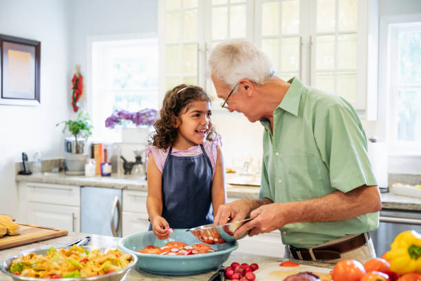 Laughing Hispanic grandfather and granddaughter in kitchen stock photo