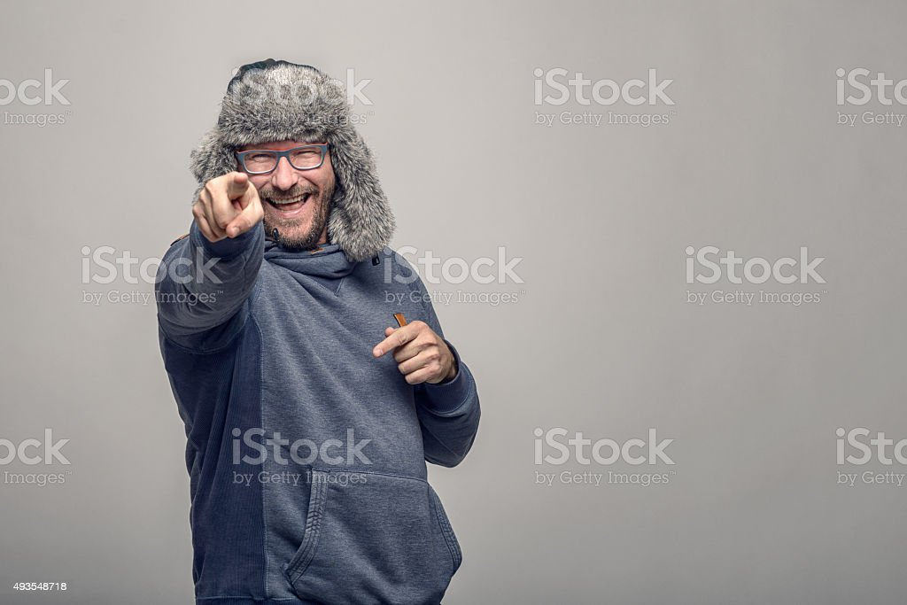 Laughing jovial man pointing at the camera stock photo