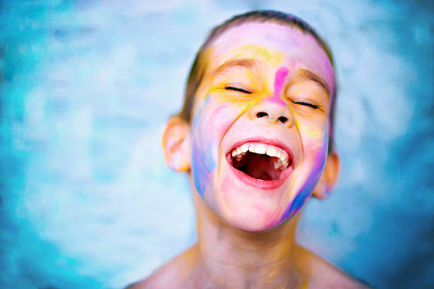 laughing kid with paint stained face stock photo