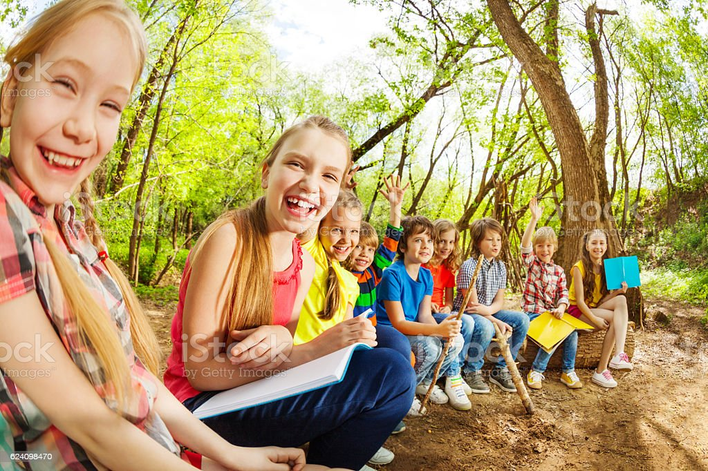 Laughing kids sitting on a log in the summer camp stock photo