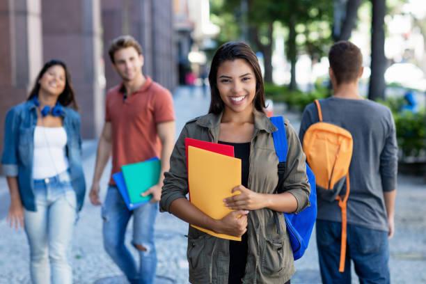 Riendo latina americana joven adulta mujer caminando en la ciudad con grupo de estudiantes - foto de stock