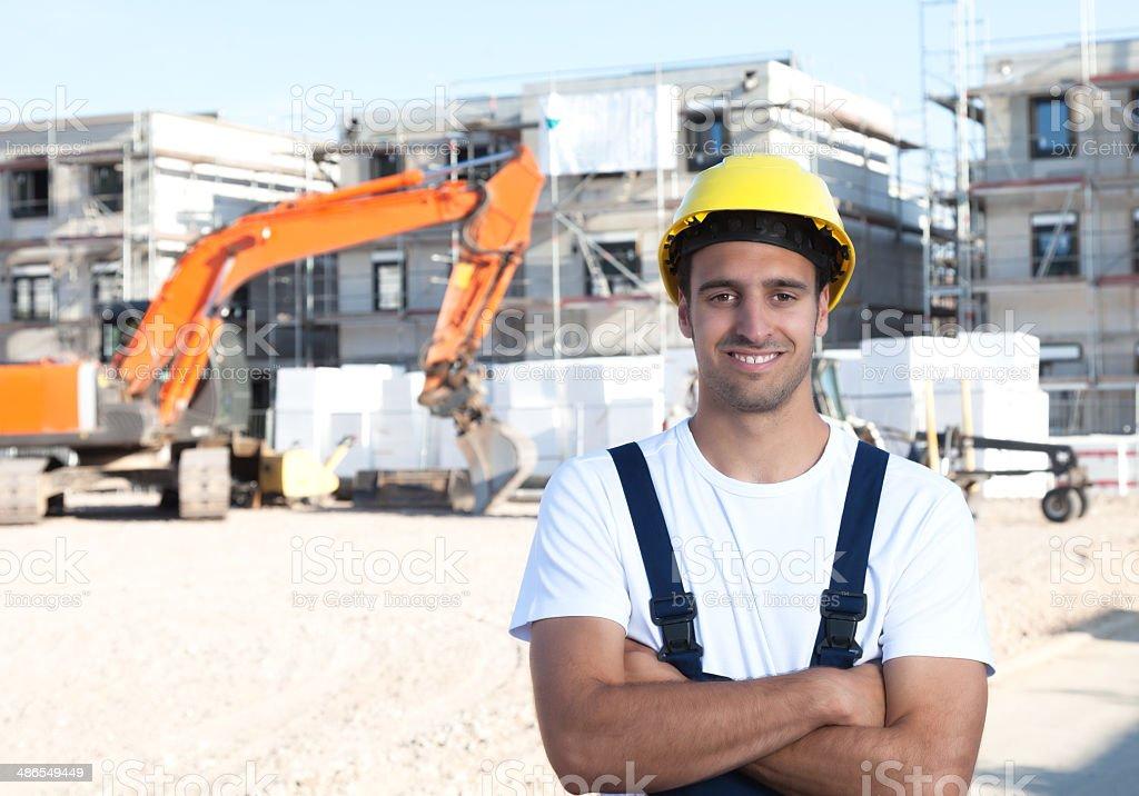 Riendo Latina Trabajador de construcción con los brazos cruzados excavator y rojo - foto de stock