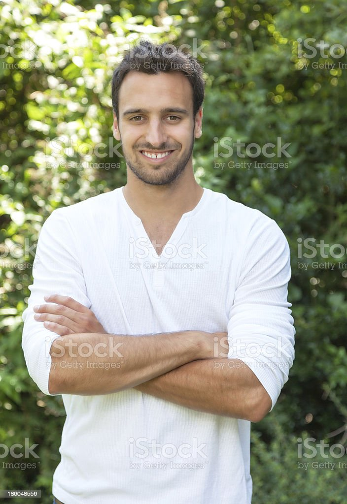 Laughing latin man with crossed arms in a park royalty-free stock photo