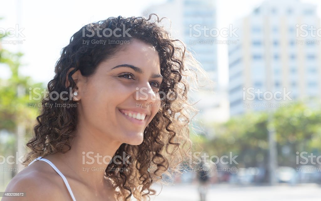 Laughing latin woman outside in the city stock photo