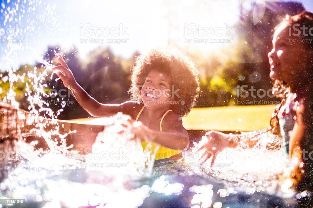 Laughing little Afro girl splashing with friends in a pool stock photo