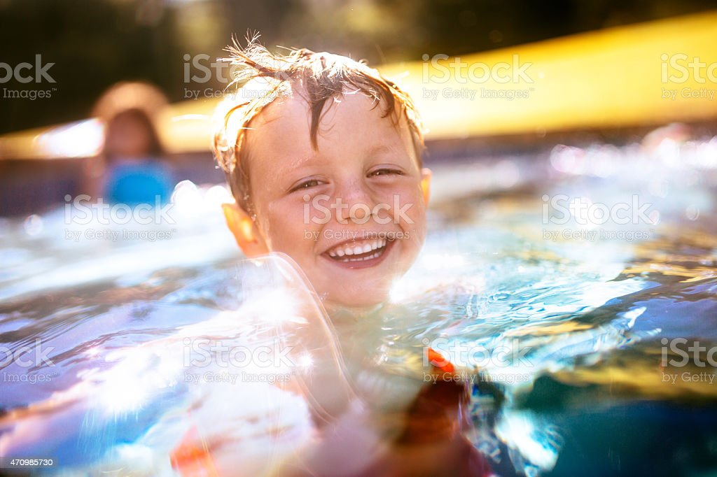 Laughing little boy playing in the swimming pool stock photo