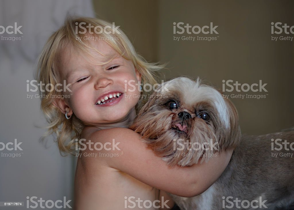 laughing little girl hugging her dog, indoors.