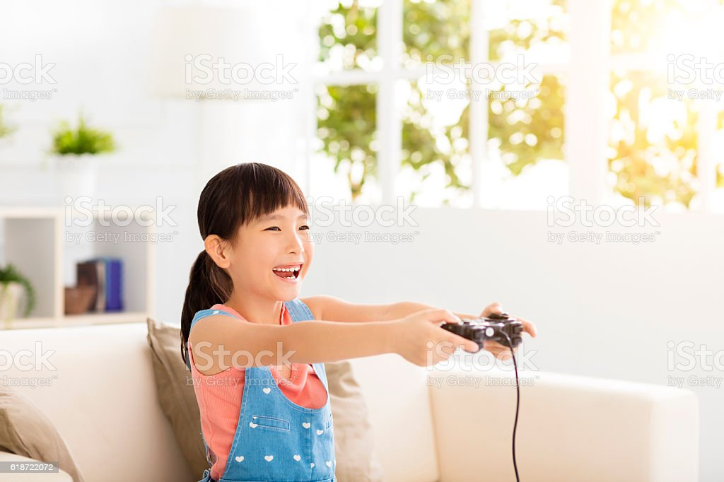 Laughing little girl playing video games on sofa royalty-free stock photo
