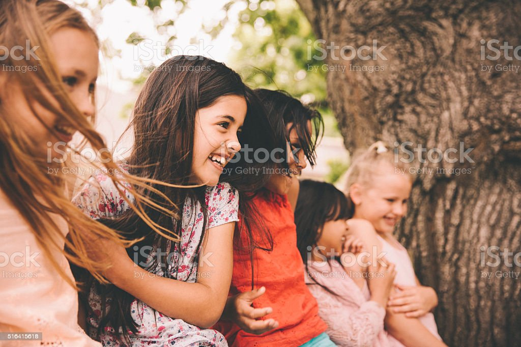 Laughing little girl with her friends in a park stock photo