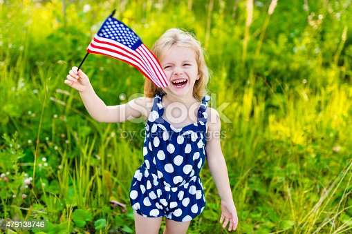 514069232 istock photo Laughing little girl with long blond hair holding american flag 479138746