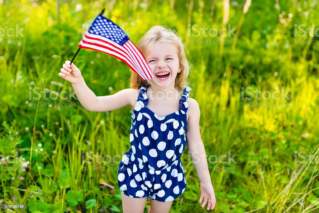 Laughing little girl with long blond hair holding american flag stock photo