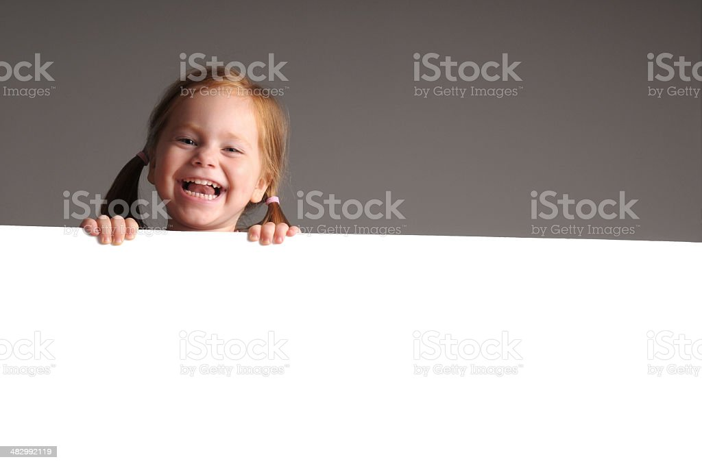 Laughing Little Redhead Behind a Blank White Sign royalty-free stock photo