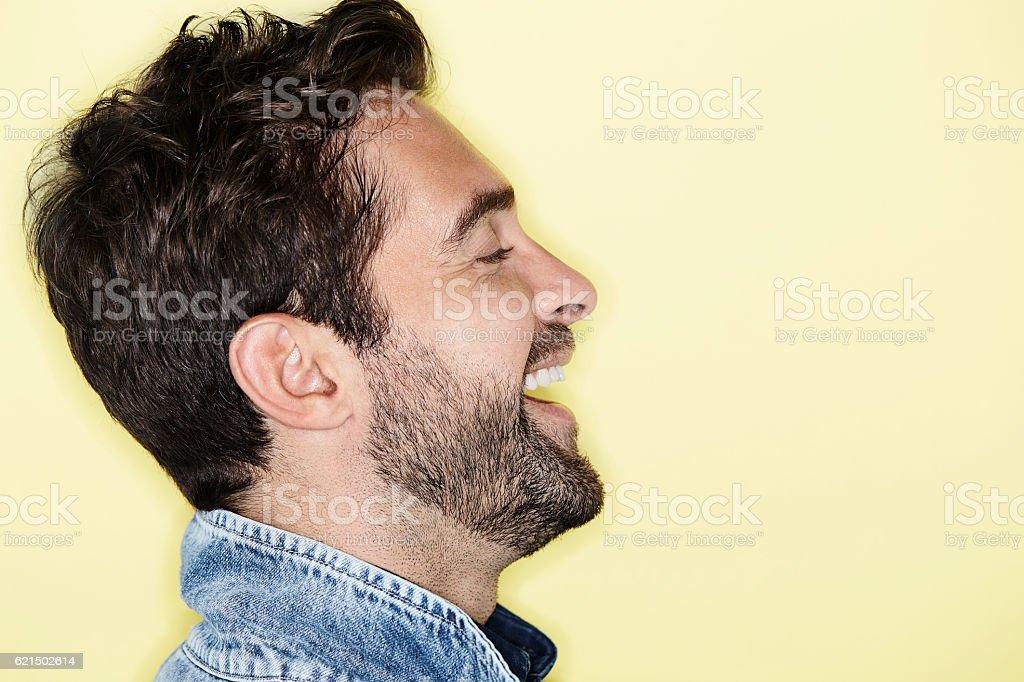 Laughing man against yellow background, profile photo libre de droits