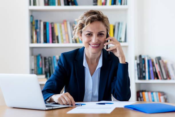 Riendo madura mujer de negocios adulta hablando en el teléfono - foto de stock