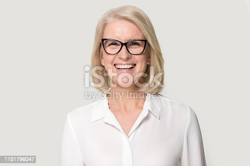 istock Laughing mature businesswoman wearing glasses posing on grey studio background 1151796047