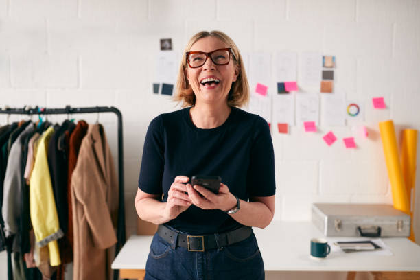 Laughing Mature Businesswoman With Mobile Phone In Front Of Desk In Start Up Fashion Business stock photo