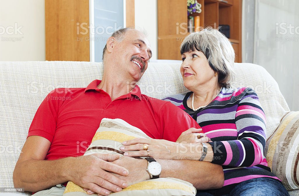 Laughing mature couple relaxing on couch royalty-free stock photo