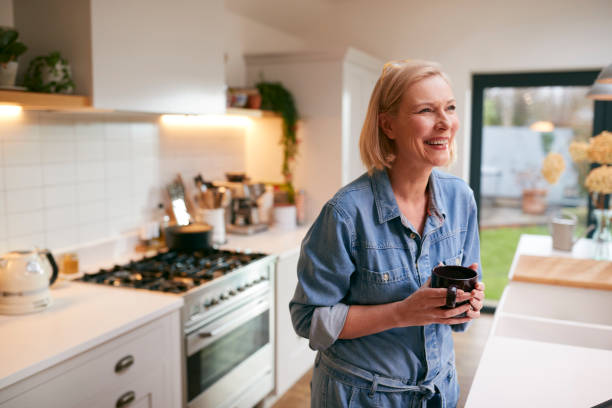 Laughing Mature Woman At Home In Kitchen Drinking Coffee stock photo