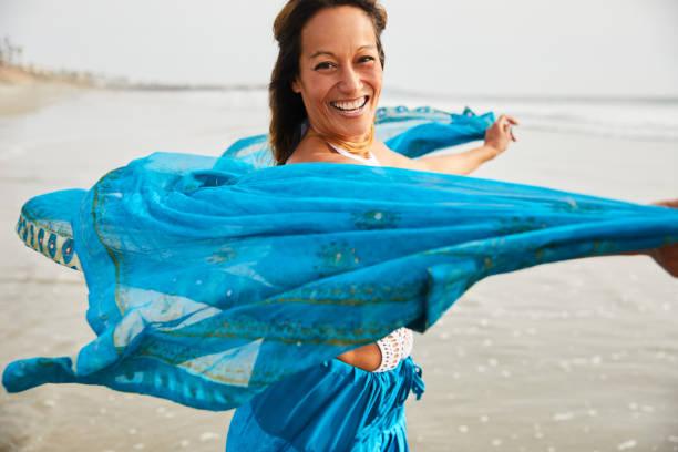 Lachende reife Frau tanzt an einem Strand mit einem türkisen Wrap – Foto