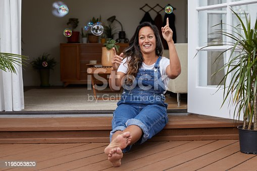 Mature woman sitting on her living room patio and laughing while popping soap bubbles