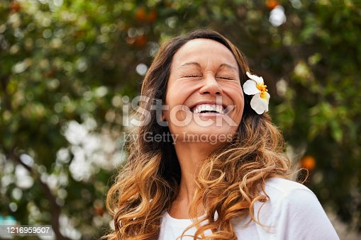 Laughing mature woman standing outside in her yard on a sunny afternoon with a flower in her long brown hair