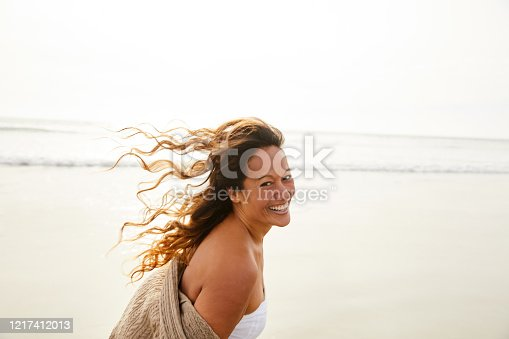 Portrait of a laughing mature woman with tousled long brown hair walking on a sandy beach in the late afternoon
