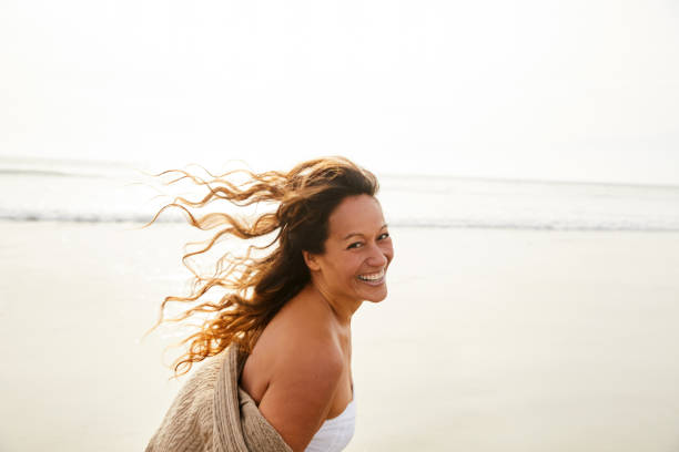 Laughing mature woman walking on a beach on a breezy afternoon stock photo
