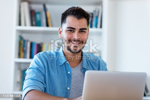 1127582480istockphoto Laughing mexican hipster man at work with laptop 1127581005